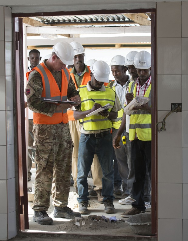Staff Sergeant Johnson from 62 Works Group Royal Engineers checking over the buildings of the Ebola Treatment Centre with the Sierra Leone contractors.