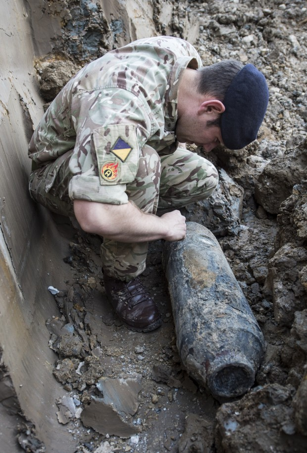 A British Army bomb disposal expert inspects the World War Two German bomb.