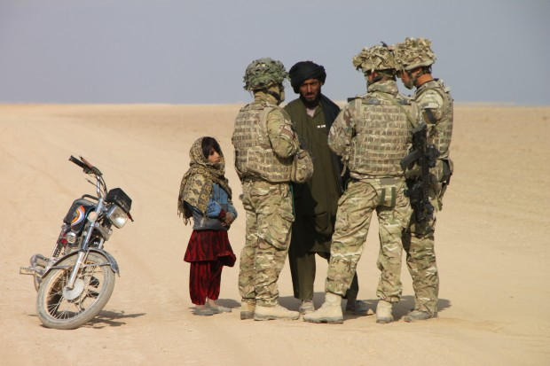 Two soldiers and an interpreter from the Queen's Royal Lancers (QRL) speak with an Afghan motorcyclist in Northern Helmand while his daughter looks on. The Queen's Royal Lancers are 12 Mechanized Brigade's Reconnaissance Regiment based in Catterick, North Yorkshire. This image was a winner in the Army Photographic Competition 2013.