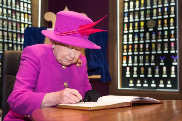 Pictured: HM The Queen makes the first signature of the Visitors Book, within the Briefing Room that Her Majesty opened moments earlier on Thursday 5th November 2015 on a visit to Imjin Barracks, Gloucester. The Queen visited the the Defence Business Service (DBS) and the Headquarters of NATO's Allied Reaction Corps (HQ ARRC) at Imjin Barracks, Gloucester. During Her Majesty's visit to Innsworth House on the base, the Queen also opened a new briefing room at the MOD's Joint Casualty and Compassionate Centre (JCCC) and the MOD Medal Office (MODMO). The Queen was given a tour of MODMO which assesses, engraves and issues awards of all UK military and selected civilian medals to serving personnel, veterans and their next of kin. The Queen was introduced to staff who prepare and engrave medals and honours for dispatch to recipients across the UK and worldwide. MODMO also uses the Elizabeth Cross to the next of kin of Armed Forces personnel who die on operations or killed by acts of terrorism. The Queen was introduced to members of the Brynin family, relatives of Lance Corporal James Brynin who was killed on operations in the Nahr-e-Sarah area of Afghanistan on 15 October 2013. The Queen toured the JCCC, MOD's permanently manned operational centre for casualty administration, the notifying of a casualty's next of kin and requests for overseas compassionate travel for members of the British Armed Forces serving overseas, anywhere in the world. Her Majesty met the team who assist braved families deal with the administrative challenges following a death, such as wills, and visited the Commemorations Team that manages the delicate process of caring for identifying and finally laying to rest the human remains of fallen heroes from pervious campaigns from as far back as WW1. If possible the team also traces the surviving family members of the deceased. The Queen was then invited to officially open the MODMO and the JCCC's new briefing room at Innsworth House, where she u