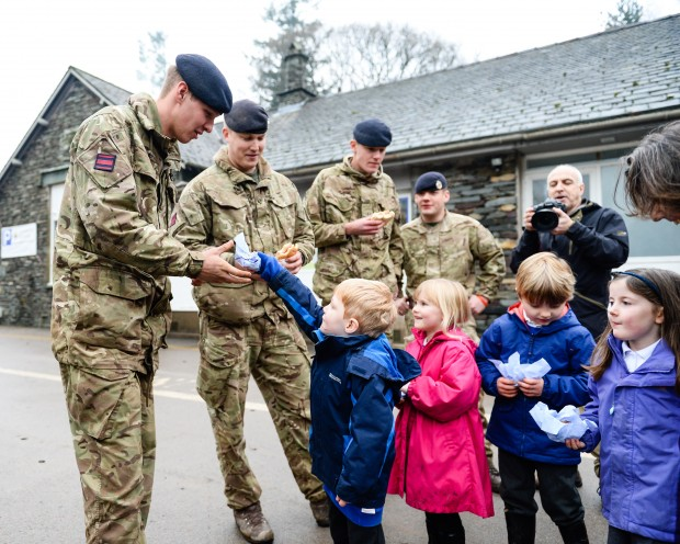 Soldiers from the Royal Engineers who have been clearing rubble and abandoned vehicles from a vital route in Cumbria have been thanked for their efforts by local schoolchildren. Pupils at Grasmere Primary School invited personnel from 21 Engineer Regiment to lunch so they could show their gratitude for the efforts being made by the military, alongside Cumbria County Council, to clear the A591. Pictured: Personnel from 21 Engineer Regiment receive bacon rolls, tea and cake from children from Grasmere Primary School. Photographer: Cpl Timothy Jones RLC; Crown Copyright