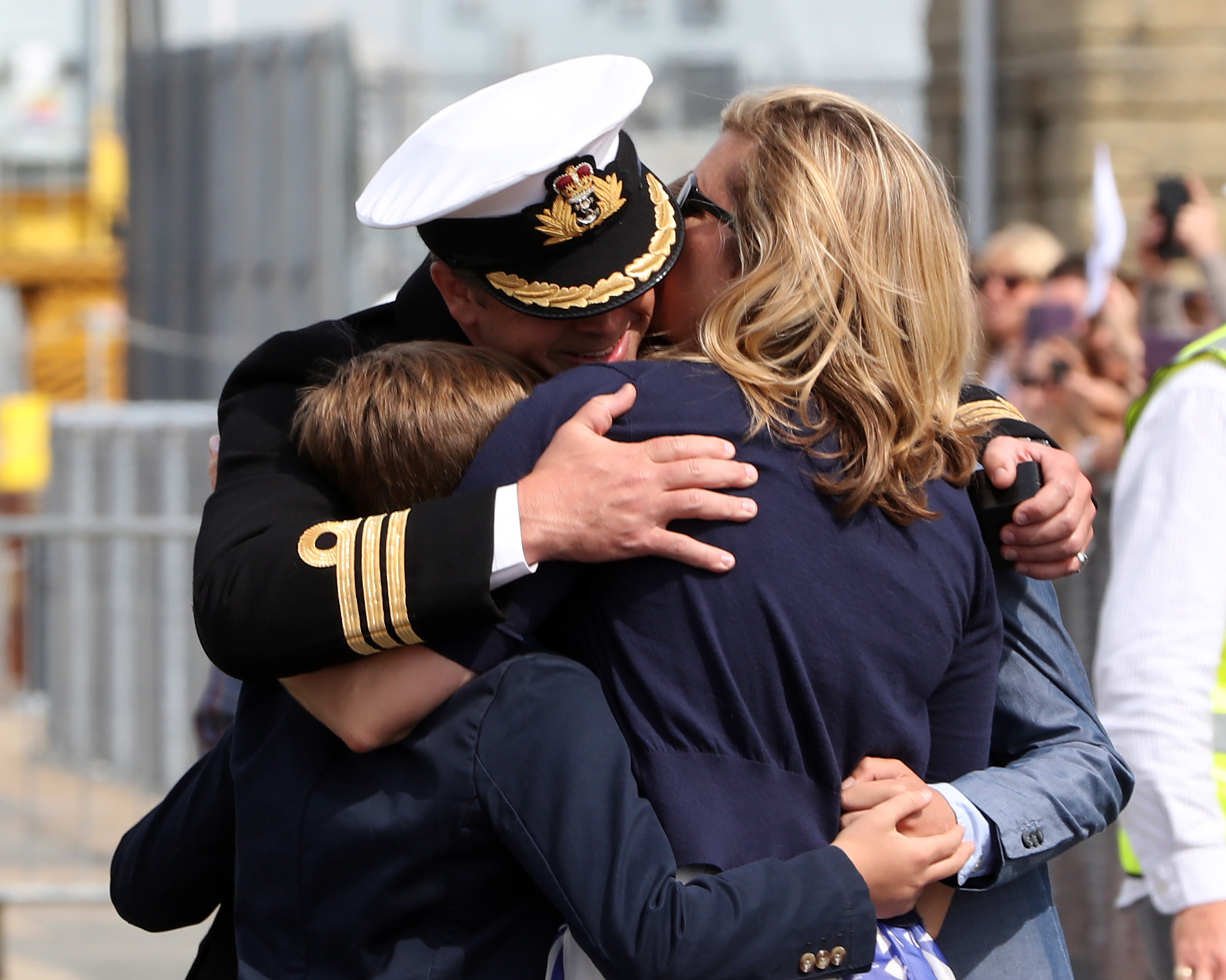 Pictured: Commander Hutchings, CO of HMS St.Albans, welcomed home by his family.
