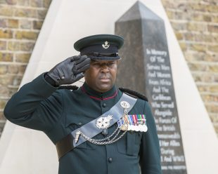 Major Larry Davis salutes as the Last Post is sounded  after the unveiling of the African and Caribbean War Memorial in Windrush Square, Brixton.