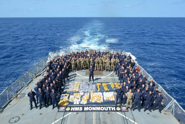 The Ship's Company of HMS Monmouth with the drugs recovered from a fishing dhow intercepted in the Indian Ocean.