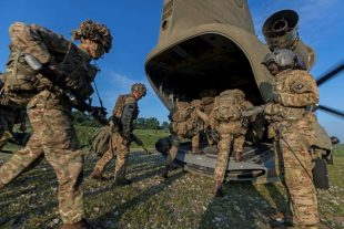 Grenadier Guards getting on a US Chinook helicopter during Exercise NOBLE JUMP taking place in Romania. The Defence Secretary will meet personnel involved in the NATO exercise on a visit to Romania today. Crown Copyright.