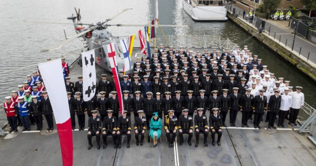 Image shows HRH The Queen with HMS Sutherland's ships company and the First Sea Lord on the ships flightdeck.