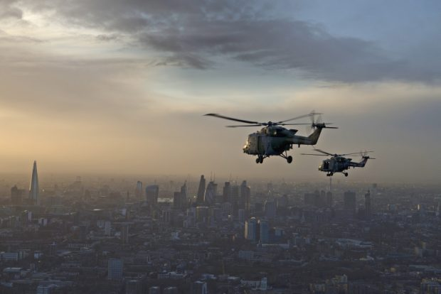 mage shows two Lynx helicopters on their last flight flying over London at sunset.