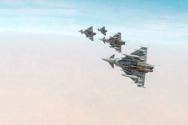 The image shows four triangular shaped fighter jets against a pinky-blue sky
