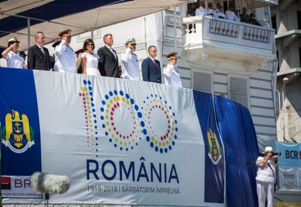 Service personnel in uniform line up behind a white flag with blue vertical borders and '100 Romania' written in a series of different coloured dots.