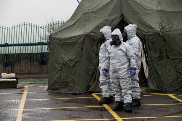 Three individuals are wearing grey personal protective equipment body suits and black face masks. There is a large green tent in the background. The individuals are standing on tarmac.