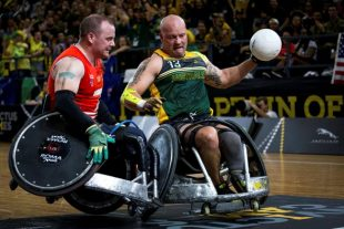 Australian Invictus Games wheelchair rugby player Peter Arbuckle (right), scores a try during the wheelchair rugby final against the United Kingdom at Sydney Olympic Park. Peter Dunning (left) from Team UK is seen here putting up a strong defence.
