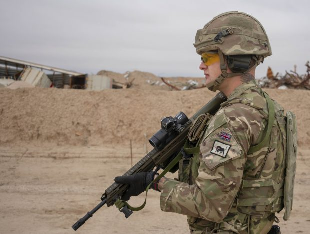 An Army soldier patrols a location in Iraq carrying a rifle.