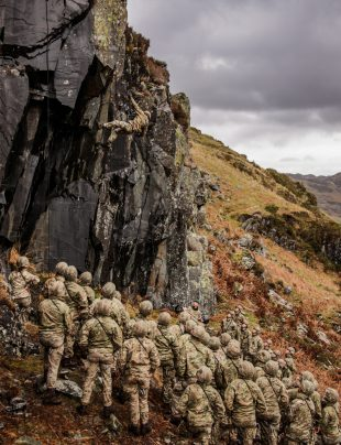 Royal Marines abseiling from a cliff