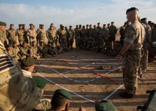 A British soldier assigned to Task Force Besmaya uses engineer tape to teach a class of Iraqi soldiers where improvised explosive devices (IED) are likely to be placed during an IED course at the Besmaya Range Complex, Iraq.
