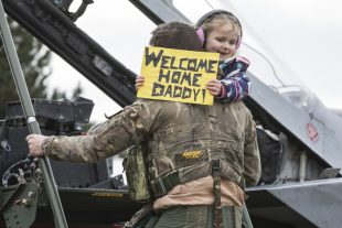 Squadron Leader Bonning descending the steps of a Tornado aircraft whilst holding his daughter.