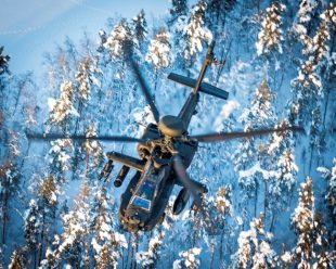 An Apache flying over snow