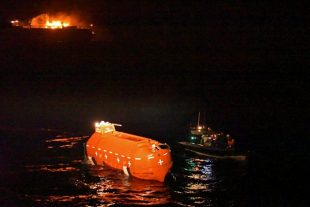 The crew of HMS Argyll, in their Rigid Hull Inflatable Boat, nudge the lifeboat of Grande America towards HMS Argyll, as the cargo ship burns in the background.