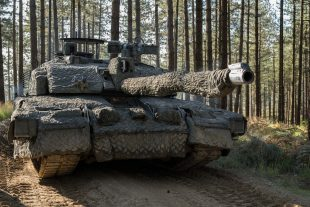 A British Army tank adorned with camoflague in a forest