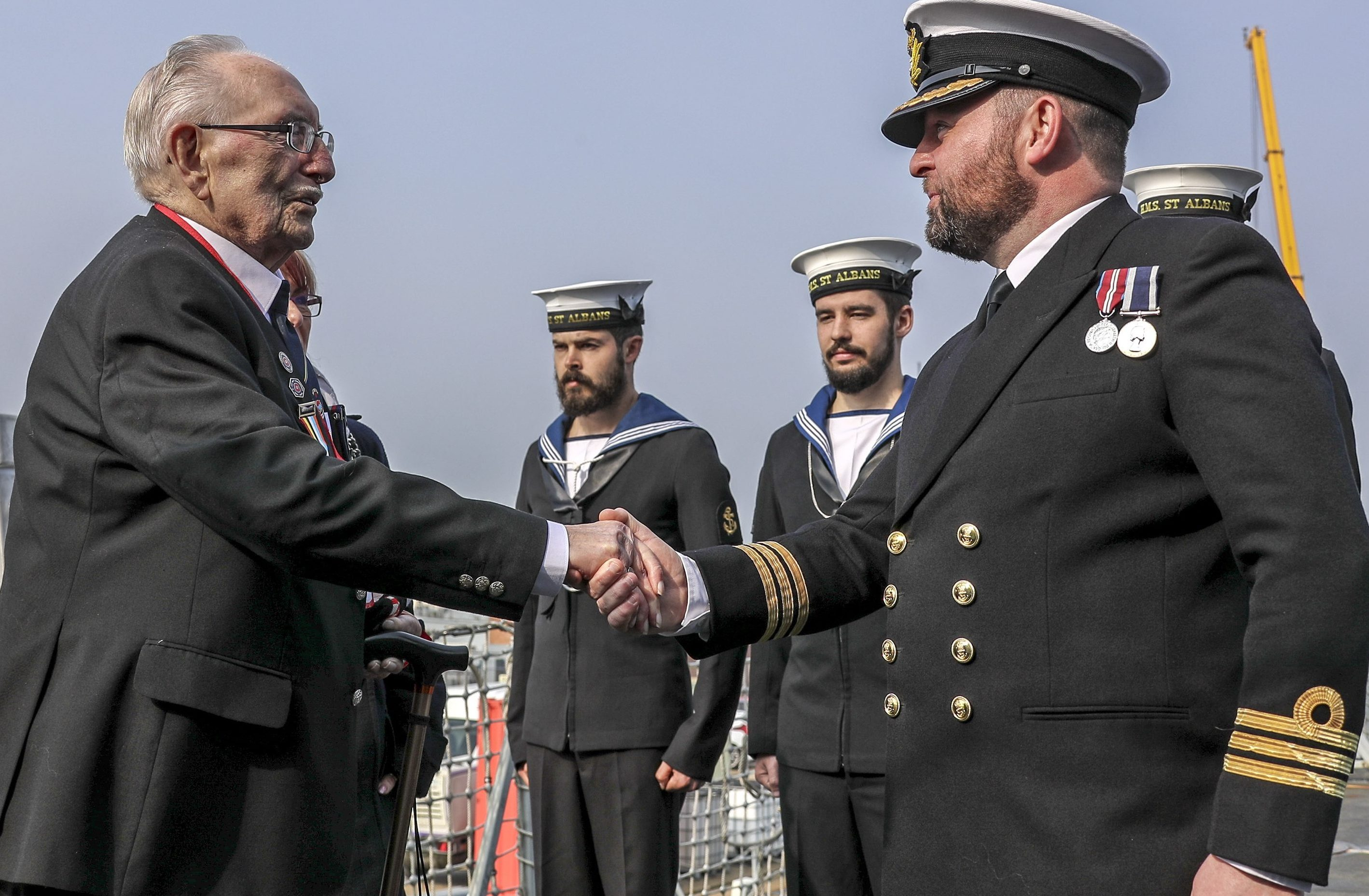 D-Day veteran, Leonard Williams, shakes hands with the Commanding Officer of HMS Saint Albans on board the ship, with two navy sailors standing to attention in the background.