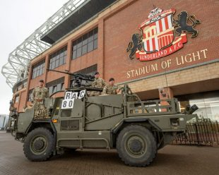 A British army Jackal and its crew parade next to Sunderland A.F.C The Stadium of Light football ground.