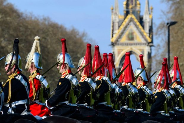 A row of Blues and Royals soldiers and officers on horseback in front of the Albert Memorial in Hyde Park.