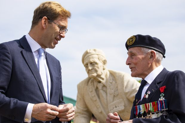 Defence Minister Tobias Ellwood talks to a Normandy veteran at the D-Day Garden. They are in front of a statue of another veteran that is part of the garden.