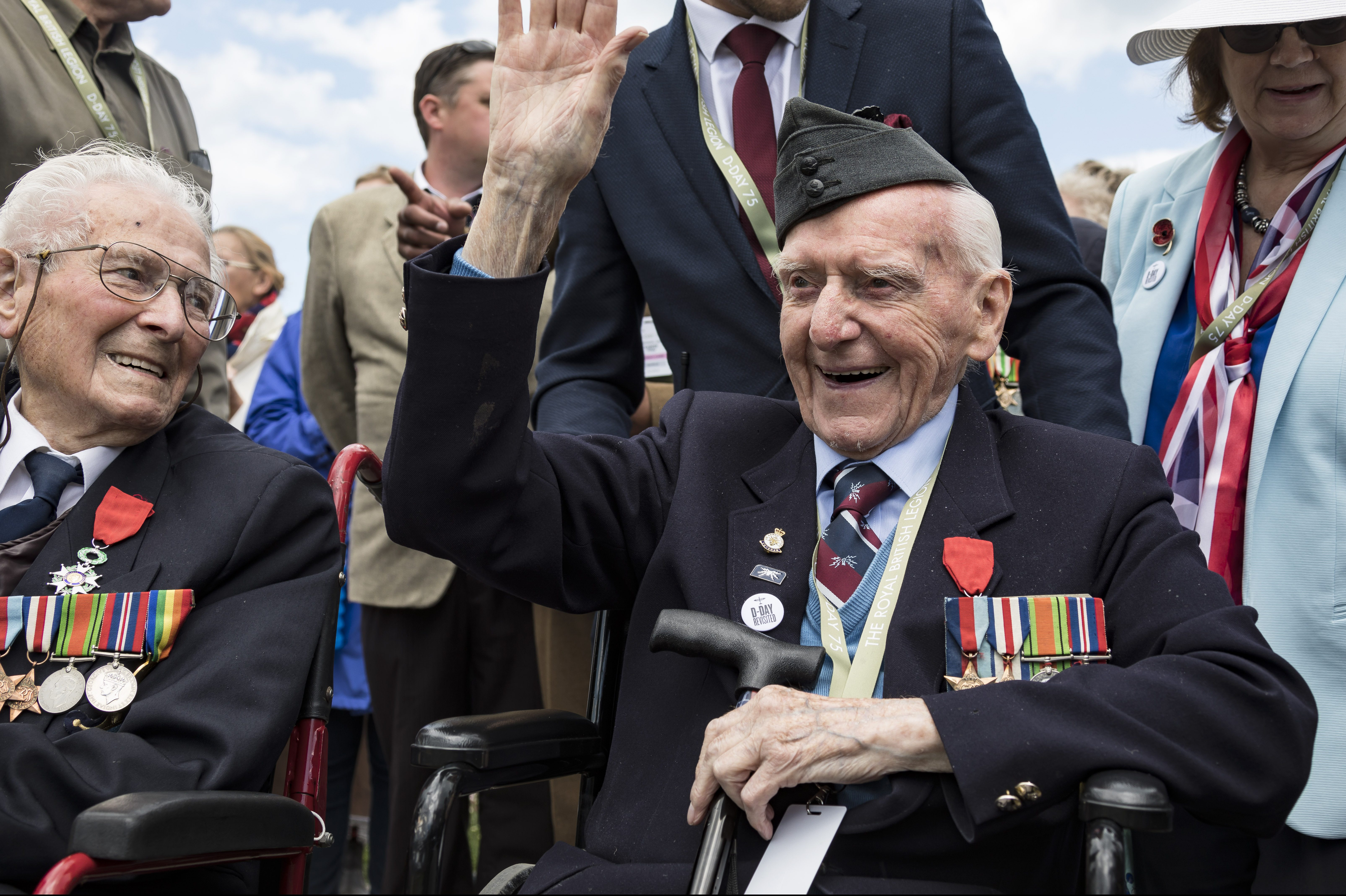 A veteran wearing a military beret and medals smiles and waves from his wheelchair