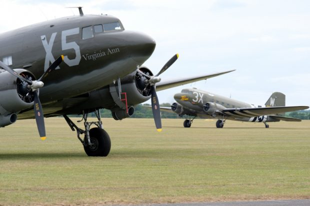 Two World War 2 Dakota aircraft preparing to take off on a runway.
