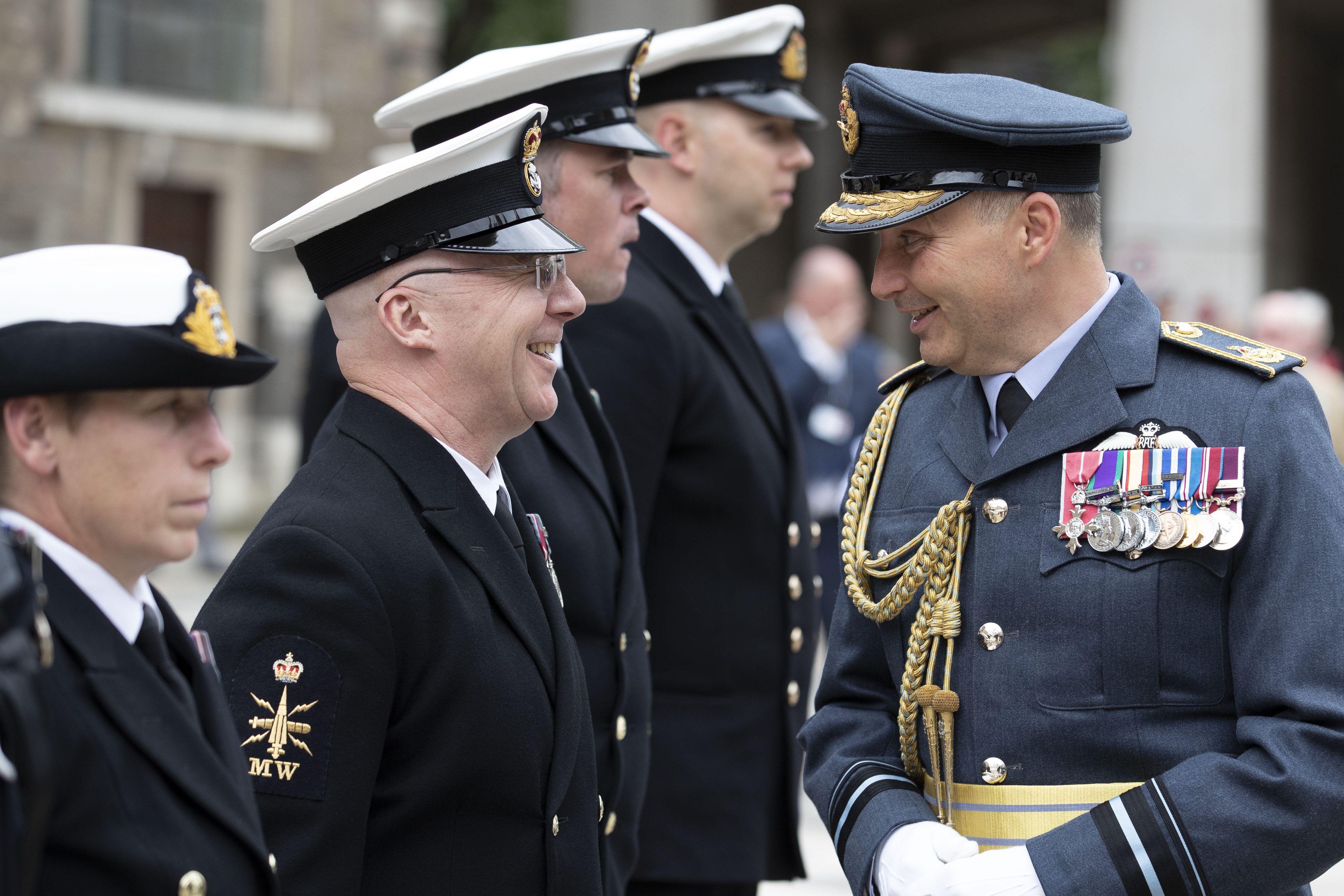 Air Vice-Marshal Ian Gale greets members of the Armed Forces who are lined up in uniform.