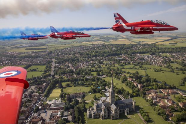 The view from the cockpit of a Red Arrows aircraft, showing the Red Arrows in formation over Salisbury Cathedral