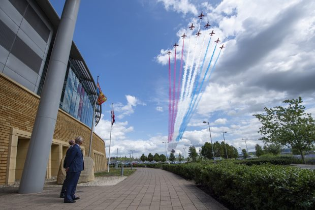 The Prince of Wales watches a formation of Red Arrows flying over the GCHQ building, leaving a red white and blue trail behind them.
