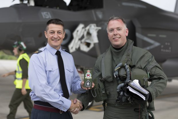 Station Commander, Group Captain Ian Townsend shakes hands with Wing Commander Scott Williams and presents the squadron patch to him in front of an F-35B jet