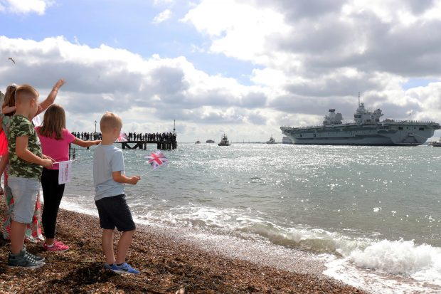 Four children wave off HMS Queen Elizabeth from a beach, while the aircraft carrier sails past in the background