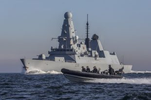 HMS Defender at sea with one of her seaboats