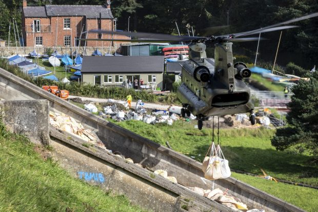 An RAF Chinook hovers over a dam in response to the emergency at Whaley Bridge