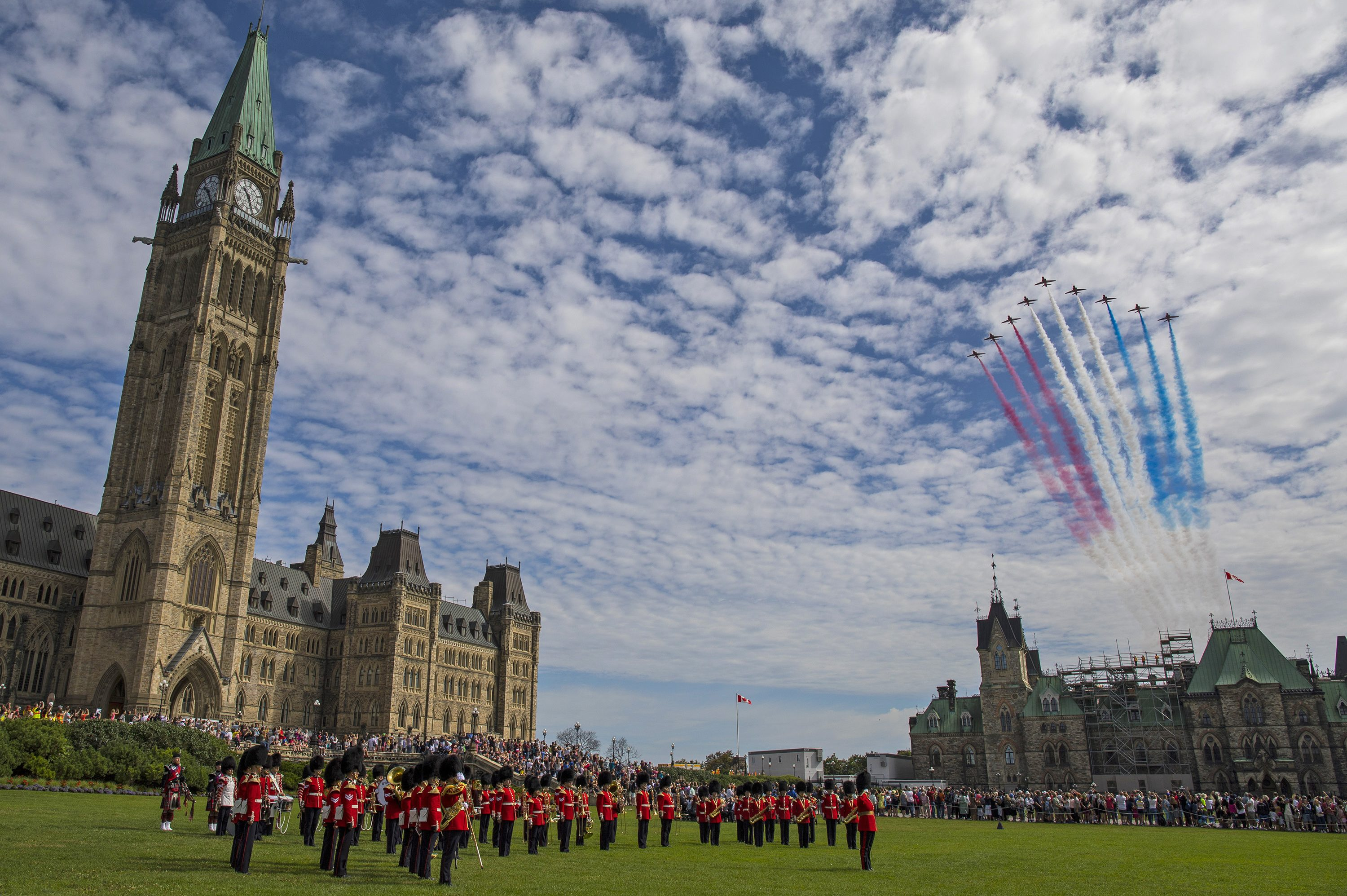 The Red Arrows fly in formation over the peace tower and a military parade as they change the guard in Ottawa, leaving a red white and blue jet trail behind them