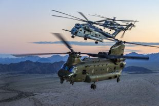 Three military helicopters fly over some mountains.
