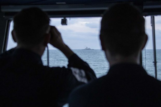 Royal Navy sailors watch a Russian ship pass them from HMS Mersey