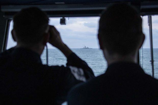 Royal Navy sailors watch a Russian ship pass them from HMS Mersey