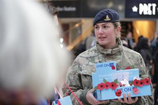 Troops and veterans selling poppies to the public at Waterloo Station during London Poppy Day